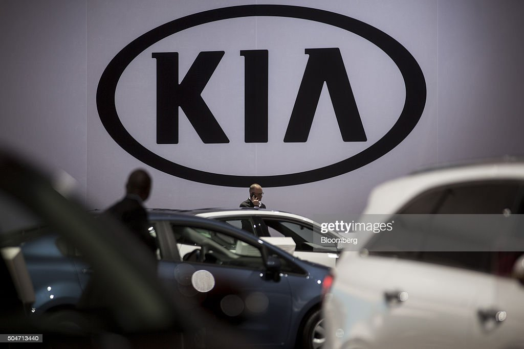Kia Motors Corp. signage stands above vehicles at the company's booth during the 2016 North American International Auto Show (NAIAS) in Detroit, Michigan, U.S., on Tuesday, Jan. 12, 2016. Last year's auto show featured 55 vehicle introductions, a majority of which were worldwide debuts, and was attended by over 5,000 journalists from 60 countries. Photographer: Andrew Harrer/Bloomberg via Getty Images