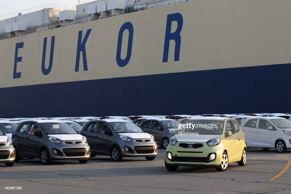 Kia Motors Corp. vehicles bound for export are driven in front of a Eukor Car Carriers Inc. roll-on/roll-off (RORO) cargo ship at the port of Pyeongtaek in Pyeongtaek, South Korea, on Monday, Sept. 30, 2013. South Koreas consumer confidence sank to a five-month low in September, even after a rebound in exports fueled the fastest economic growth in two years last quarter. Photographer: SeongJoon Cho/Bloomberg via Getty Images