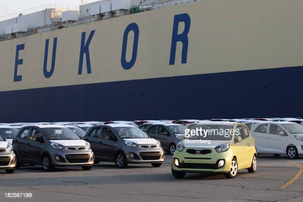Kia Motors Corp vehicles bound for export are driven in front of a Eukor Car Carriers Inc rollon/rolloff cargo ship at the port of Pyeongtaek in...