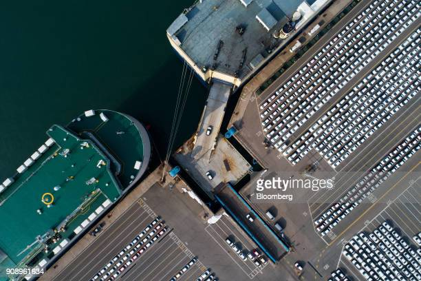 Kia Motors Corp vehicles bound for export are driven on to a Eukor Car Carriers Inc rollon/rolloff vehicles carrier cargo ship top right in this...