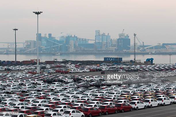 Kia Motors Corp vehicles bound for export await shipment at the port of Pyeongtaek as a cement factory operates in the background in Pyeongtaek South...