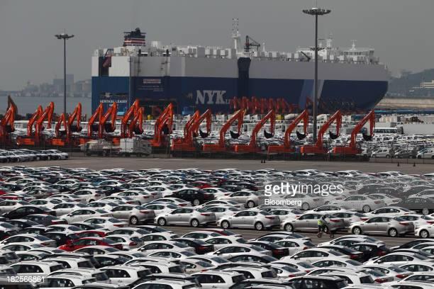 Kia Motors Corp vehicles bound for export await shipment in front of a Nippon Yusen Kaisha rollon/rolloff cargo ship at the port of Pyeongtaek in...