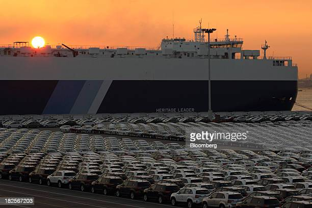 Kia Motors Corp vehicles bound for export await shipment in front of a Nippon Yusen Kaisha rollon/rolloff cargo ship at sunset at the port of...