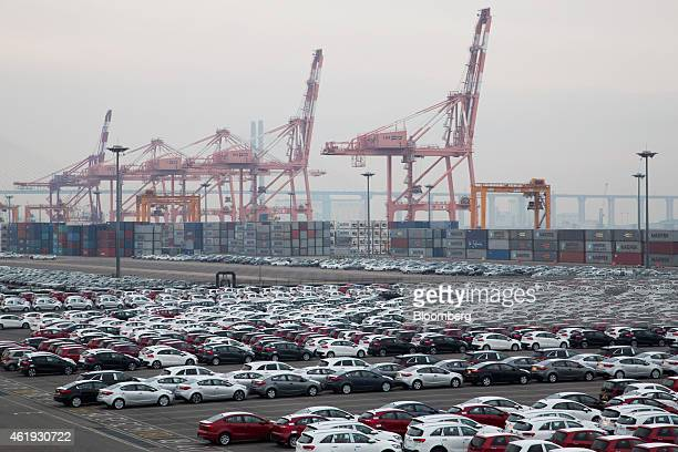 Kia Motors Corp vehicles bound for export await shipment near stacked containers and gantry cranes at the port of Pyeongtaek in Pyeongtaek South...
