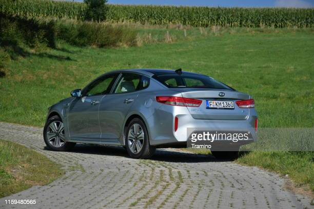 kia optima plug-in hybrid vehicle on the road - alternative fuel vehicle stock pictures, royalty-free photos & images