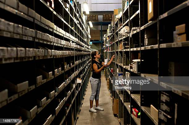 Kiandra Gadison looks for an item as she fills customer orders at the JC Whitney distribution center in La Salle Illinois US on Friday June 8 2012...