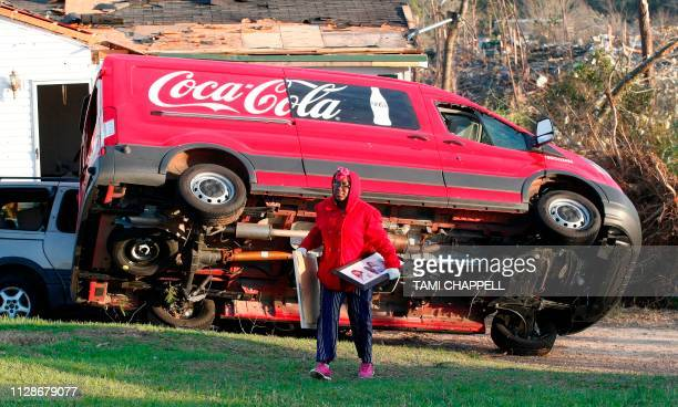 Kiara Slater removes items from her parents home after a tornado struck in Beauregard Alabama on March 4 2019 Rescuers in Alabama resumed search...