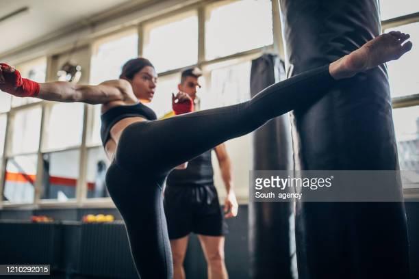 kick-box-lehrer suchen, wie frau kick boxer tritt boxsack auf kick-box-klasse - treten stock-fotos und bilder