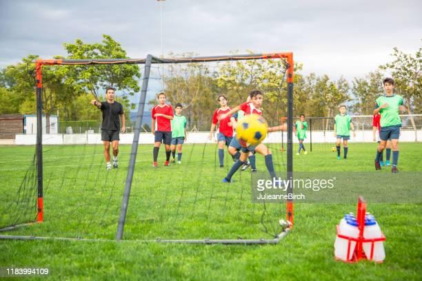 kick getting past footballer für scoring goal - jugendmannschaft stock-fotos und bilder