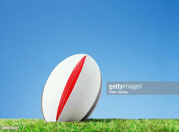 Kick off rugby ball on grass