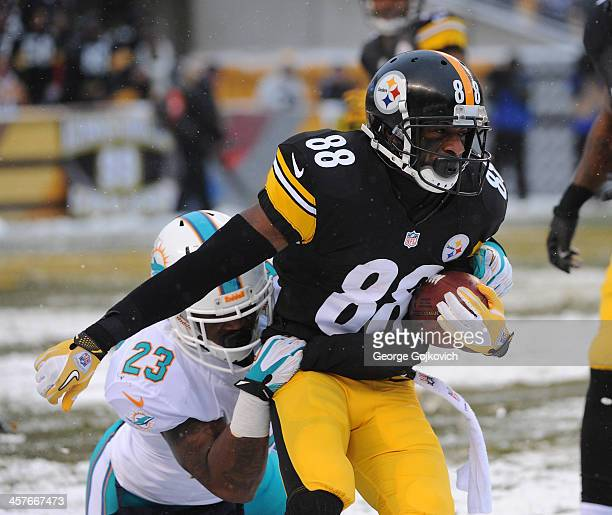 Kick returner Emmanuel Sanders of the Pittsburgh Steelers is tackled by Mike Gillislee of the Miami Dolphins during a game at Heinz Field on December...