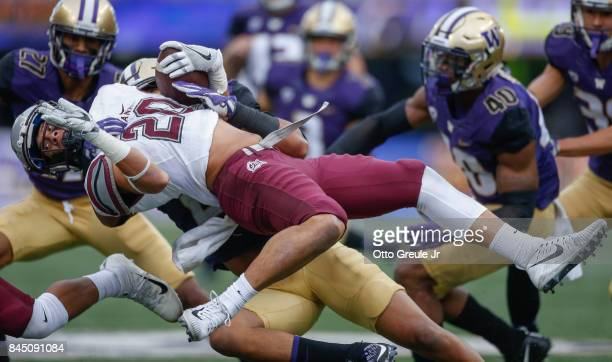 Kick returner Gavin Crow of the Montana Grizzlies is tackled by defensive back Ezekiel Turner of the Washington Huskies at Husky Stadium on September...