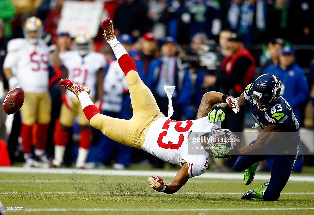 Kick returner LaMichael James #23 of the San Francisco 49ers is hit by wide receiver Ricardo Lockette #83 of the Seattle Seahawks on a return in the first half during the 2014 NFC Championship at CenturyLink Field on January 19, 2014 in Seattle, Washington.