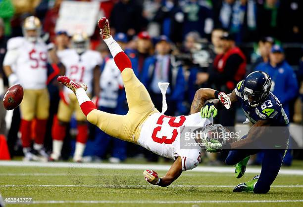 Kick returner LaMichael James of the San Francisco 49ers is hit by wide receiver Ricardo Lockette of the Seattle Seahawks on a return in the first...