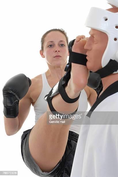 kickboxer kicking her target. - caneleira roupa desportiva de proteção imagens e fotografias de stock
