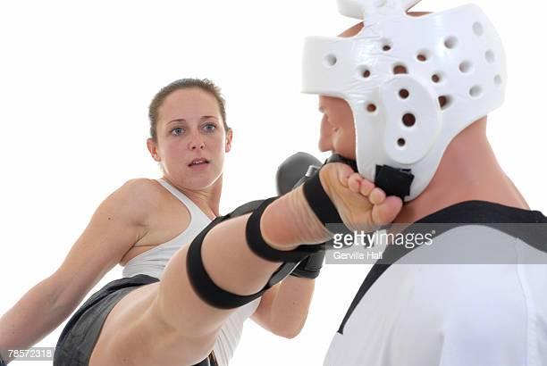 kickboxer making contact with her target. - caneleira roupa desportiva de proteção imagens e fotografias de stock