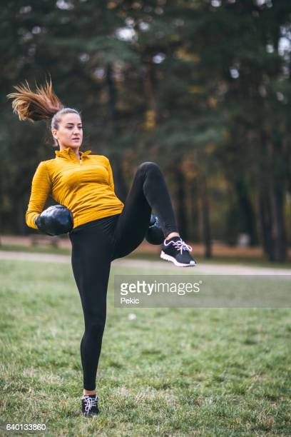 Kickboxing girl exercising high kick