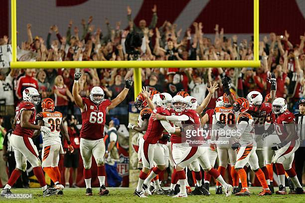 Kicker Chandler Catanzaro of the Arizona Cardinals is congratulated by Drew Butler and Mike Leach after Catanzaro kicked the game winning field goal...