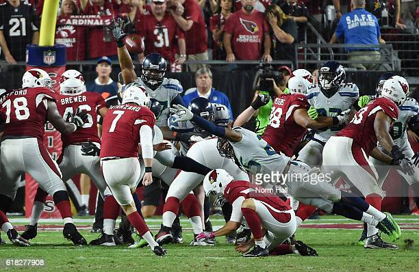 Kicker Chandler Catanzaro of the Arizona Cardinals misses a field goal in overtime as Richard Sherman and Ahtyba Rubin of the Seattle Seahawks...
