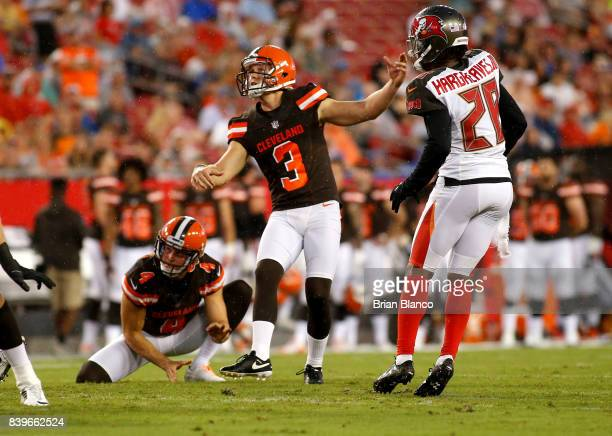 Kicker Cody Parkey of the Cleveland Browns gets a hold from punter Britton Colquitt as he kicks a 38 yard field goal in front of cornerback Vernon...