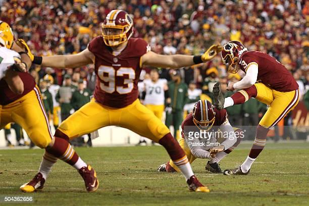 Kicker Dustin Hopkins of the Washington Redskins kicks a first quarter field goal while outside linebacker Trent Murphy blocks against the Green Bay...