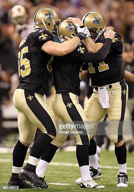 Kicker Garrett Hartley of the New Orleans Saints celebrates with teammates David Thomas and Mark Brunell after kicking a 40yard gamewinning field...
