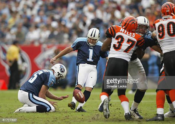 Kicker Gary Anderson of the Tennessee Titans attempts to score off a hold by punter Craig Hentrich as cornerback Reggie Myles and defensive end...