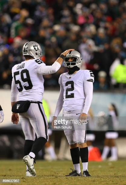 Kicker Giorgio Tavecchio of the Oakland Raiders is consoled by teammate Jon Condo after missing a field goal against the Philadelphia Eagles during...
