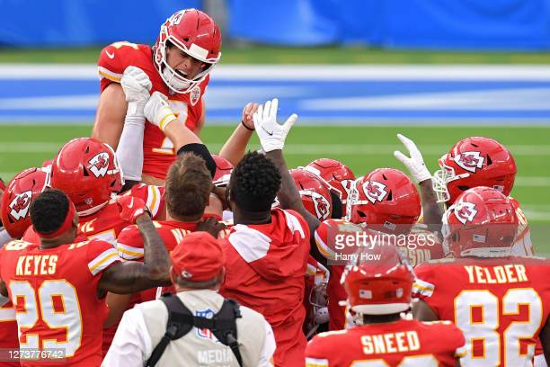 Kicker Harrison Butker of the Kansas City Chiefs celebrates with teammates after kicking the game-winning field goal against the Los Angeles Chargers...