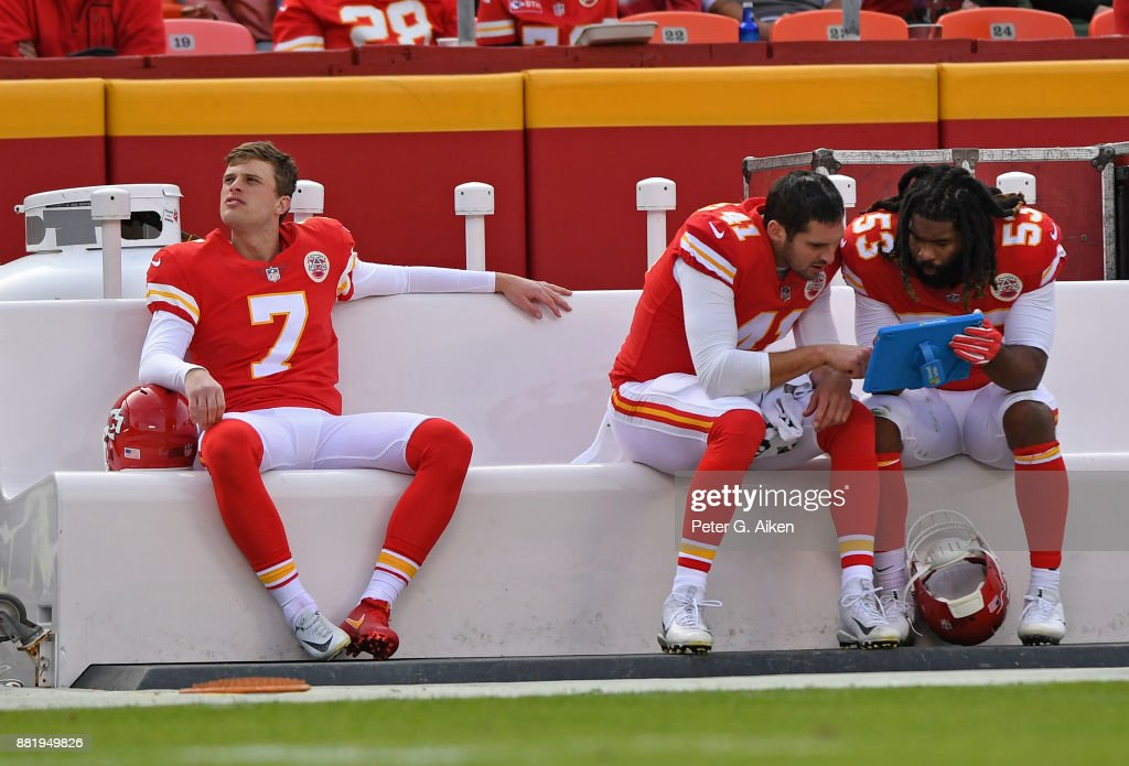 Kicker Harrison Butker #7 of the Kansas City Chiefs looks on from the bench, as teammates James Winchester #41 and Ramik Wilson #53 study a tablet against the Buffalo Bills during the second half at Arrowhead Stadium on November 26, 2017 in Kansas City, Missouri.