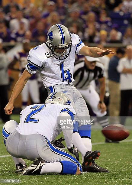 Kicker Jason Hanson of the Detroit Lions kicks as place kicker Nick Harris holds against the Minnesota Vikings at Mall of America Field on September...