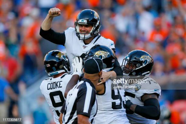 Kicker Josh Lambo of the Jacksonville Jaguars celebrates his game-winning field goal with teammates punter Logan Cooke, defensive end Calais Campbell...