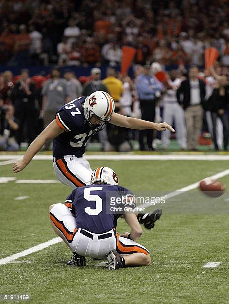 Kicker Josh Vaughn of the Auburn Tigers kicks a field goal as teammate Sam Rives holds against the Virginia Tech Hokies during the Nokia Sugar Bowl...