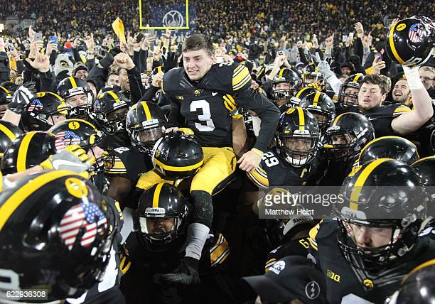 Kicker Keith Duncan of the Iowa Hawkeyes is lifted in the air by teammates after kicking the winning field goal against the Michigan Wolverines on...