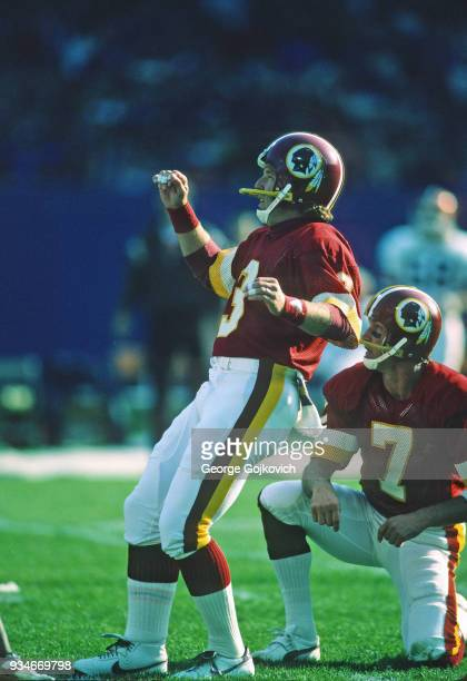 Kicker Mark Moseley of the Washington Redskins kicks on a hold by Joe Theismann during a game against the Cleveland Browns at Cleveland Municipal...