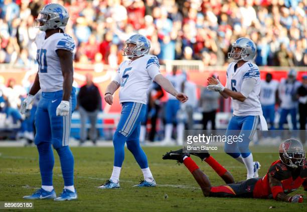 Kicker Matt Prater of the Detroit Lions joins punter Sam Martin and tight end Michael Roberts as they watch the path of his 46yard gamewinning field...
