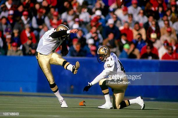 Kicker Morten Anderson of the New Orleans Saints kicks off with Toi Cook holding the ball in the kicking T during an NFL football game circa 1989...