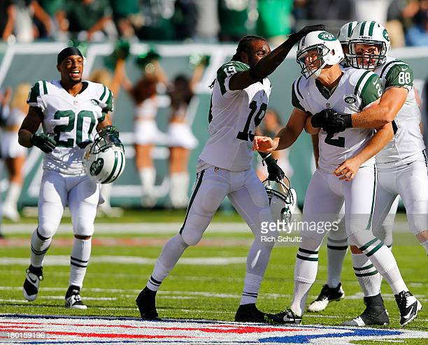 Kicker Nick Folk of the New York Jets is congratulated by teammates Clyde Gates and Konrad Reuland after kicking a game winning 48 yard field goal...