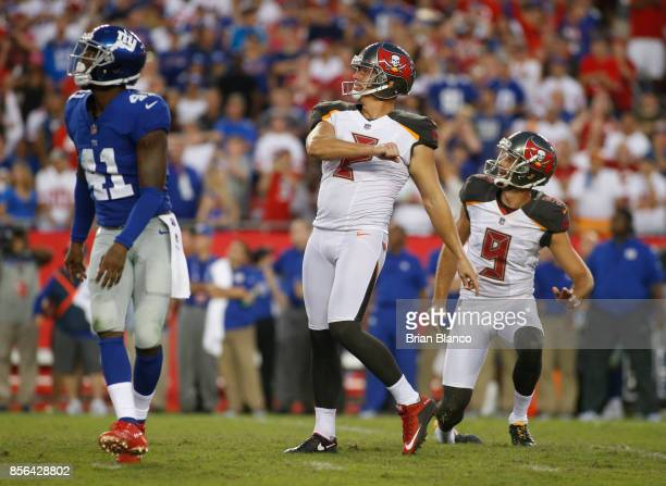 Kicker Nick Folk of the Tampa Bay Buccaneers and punter Bryan Anger join cornerback Dominique RodgersCromartie of the New York Giants in watching the...
