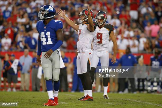 Kicker Nick Folk of the Tampa Bay Buccaneers celebrates as he and punter Bryan Anger join cornerback Dominique RodgersCromartie of the New York...