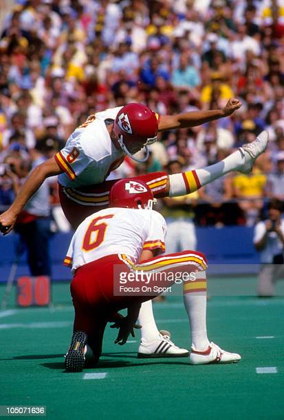 Kicker Nick Lowery of the Kansas City Chiefs kicks a field goal with punter Jim Arnold holding for him during an NFL football game circa 1985 Lowery...