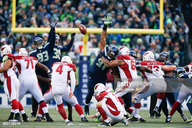 Kicker Phil Dawson of the Arizona Cardinals makes a 53 yard field goal as defensive end Dwight Freeney of the Seattle Seahawks Bradley McDougald and...