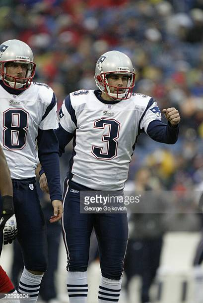 Kicker Stephen Gostkowski of the New England Patriots gestures as he walks off the field with holder Josh Miller after kicking an extra point against...