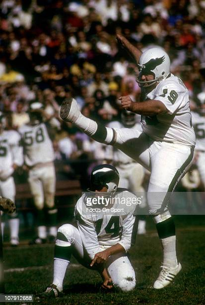 Kicker Tom Dempsey of the Philadelphia Eagles kicks a field goal with quarterback Pete Liske doing the holding during an NFL football game circa 1971...