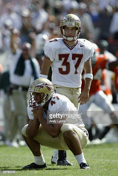 Kicker Xavier Beitia of Florida State eyes the kick as he squats on the field while holder Chance Gwaltney looks on against Miami during the game on...