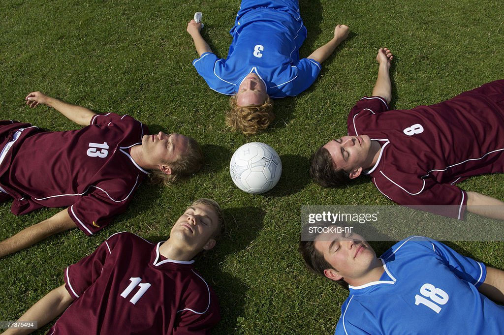 Kickers lying with closed eyes on soccer field : Photo