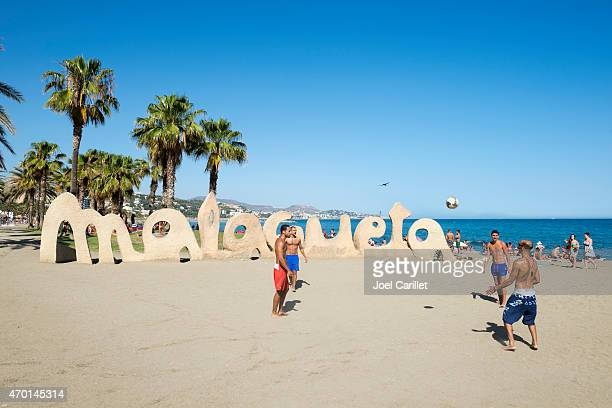 Kicking soccer ball at Playa de la Malagueta in Malaga