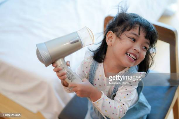 Kid activity concept.Kid girl use curlers or hair dryer drying her hair after bathing.