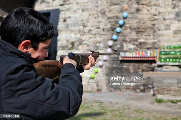 Kid aiming at a shooting gallery.
