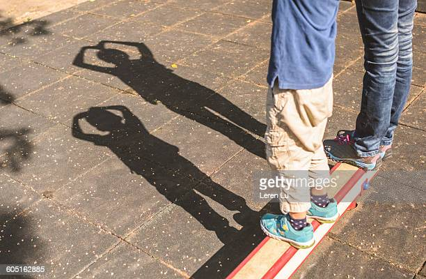 Kid and adult making heart shape shadow
